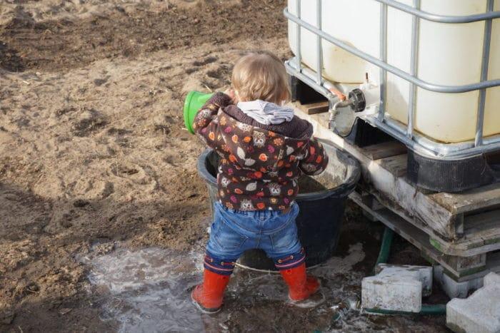 Gummistiefel und Giießkanne - Baby im Garten