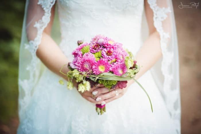 Braut mit Brautstrauß in pink und Schleier mit Spitze