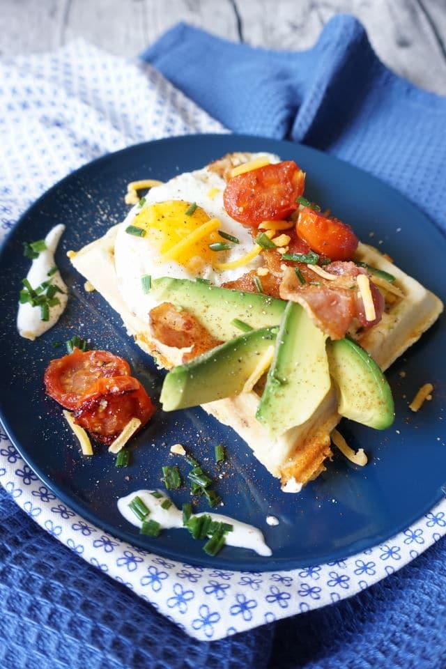 herzhafte Frühstückswaffeln auf blauem Teller, belegt mit Avocado, gebratenen Tomaten, einem Spiegelei, geriebenem Käse und gebratenem Baconscheiben - BLW Rezepte