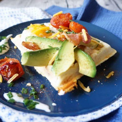 blauer Teller mit rechteckiger herzhafter Frühstückswaffel ganiert mit Avocadoschnitzen, Coktailtomaten, Spiegelei, geriebenem Käse und Bacon