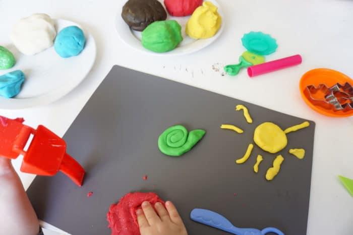 graues Brett mit einer Sonne aus gelber Knete und einer grünen Schnecle, verschiedene selbstgemachte Knete auf einem Teller