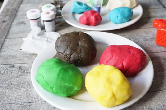 Knete selber machen one Alaun - zwei weiße Teller mit Knete in verschiedenen Farben - gelb, pink, grün, braun und grün auf einem Teller, Gllitzerknete auf dem anderen Teller - nebendran Lebensmittelfarben