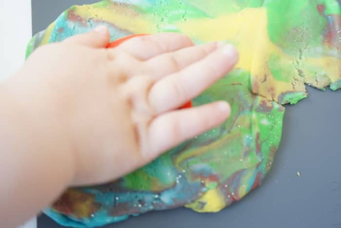 Kinderhand auf einem Haufen Knete aus verschiedenen gemischten Farben - DIY mit Kindern: selbstgemachte Knete ohne Alaun