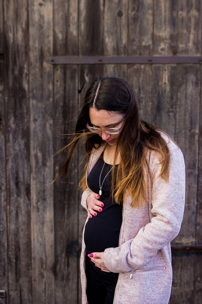 Mama in der 18. Woche schwanger, hält beide Hände an den Bauch