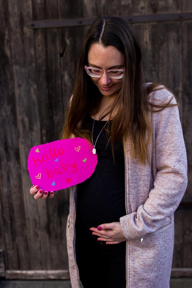 """Mama mit braunen Haaren und Brille, eine Hand auf dem Bauch, in der anderen ein Schild mit """"hallo baby"""" - zweite Schwangerschaft verkünden"""