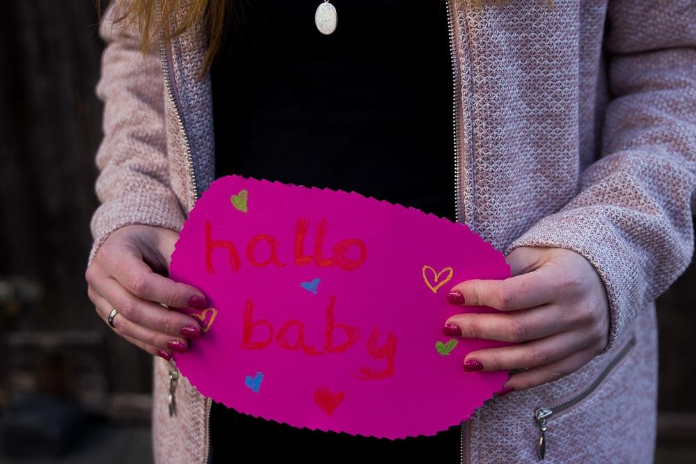 """Pinkes Schild mit orangener Aufrischt """"hallo baby"""""""