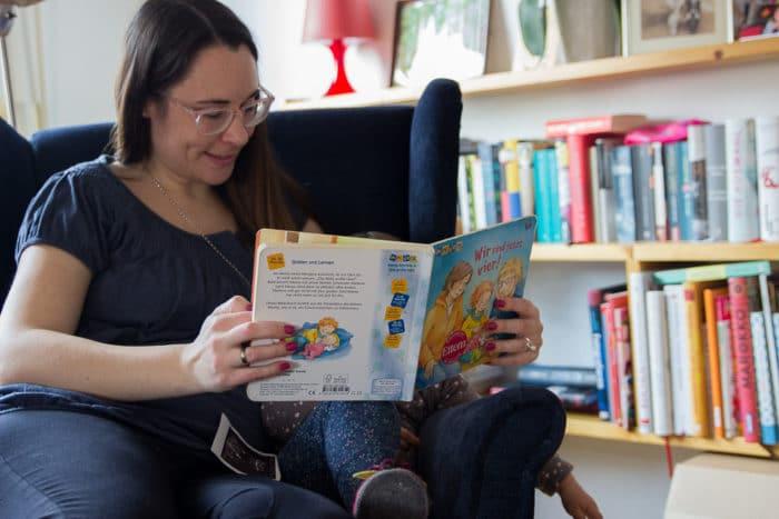 Wir sind jetzt 4 - Buch für Kinder um die zweite Schwangerschaft näher zu bringen. Mama liest ihrer Tochter auf dem Sessel sitzend vor
