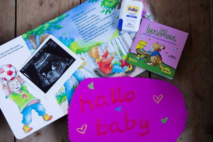 """Bild mit Ultraschallfoto eines Babys, Schild """"hallo baby"""", Buch für Kinder """"Wir sind jetzt vier"""" und Folio Tabletten"""