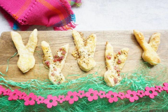 Hasenohren mit Speck und Käse aus Blätterteig - selbstegmachte Blätterteighasen auf Brett mit bunter Deko