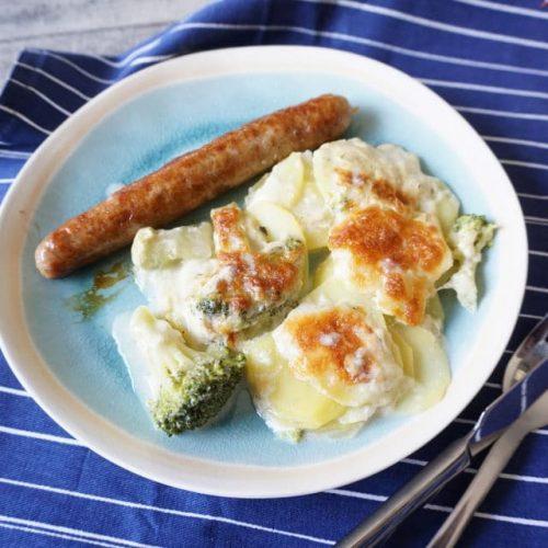 Teller mit knsurpig überbackenen Kartoffelgratin mit Brokkoli und Käse, dazu Bratwurst