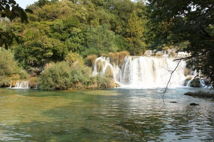 Wasserfälle und see mit grünen Büschen und Bäumen drum herum - Nationalpark Krka in Kroatien - unser Familienurlaub