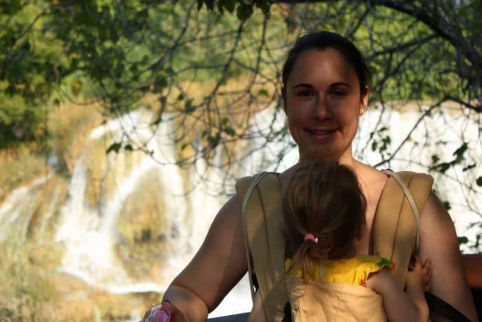 Mama mit Klinkind in der Trage vor dem Bauch - im Hintergrund die Wasserfälle im Nationalpark Krka in Kroatien