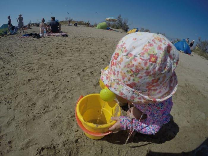 Kleinkind am Strand mit Sonnenhut, Uv Anzug und glebem Sandeimer - Strand Nin in Kroatien