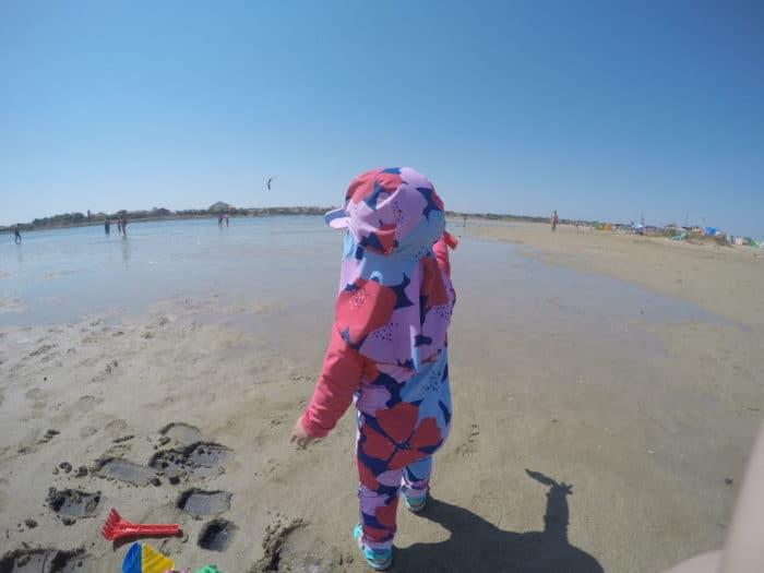 kleines Mädchen am Strand, von hinten zu sehen, steht und zeigt in Richtung Meer, hat einen bunten UV-Anzug an und Sandalen von Crocs, daneben liegt Sandspielzeug im Sand