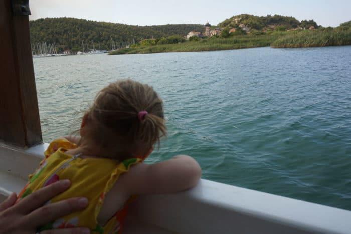 Kleinkind auf einem Ausflugsboot beim Kroatienkinderurlaub - Mädchen mit gelbem Kleind un Pferdeschwanz