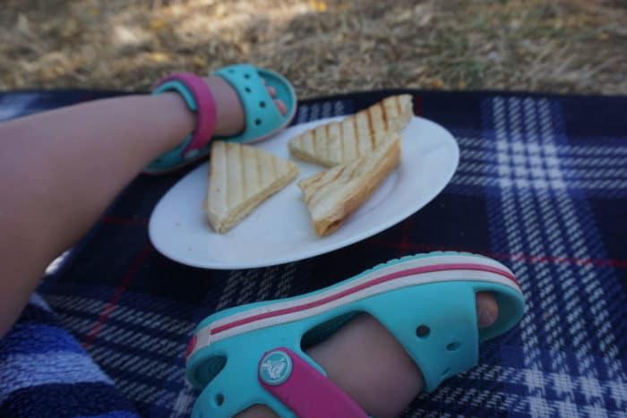 Mittagssnack für breifrei und BLW Kleinkinder im Urlaub - Sandwich auf einem Teller, danaeben Kinderfüße in mint und pink farbenen Sandalen von Crocs