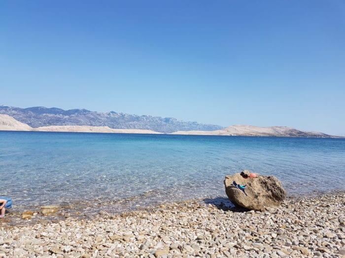 menschenleerer Kiesstrand und türkisblaubes Mee mit Blick auf Berge- Strandurlaub in Kroatien mit Kleinkind auf der Insel Pag am Beach Elena