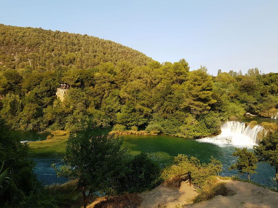 Grüne Wälder und Felslandschaft mit türkisblauem Seewasser in der Mitte - der KRka Nationalpark als Badeort im Kroatien bei unserem Strandurlaub in Kroatien mit Kleinkind