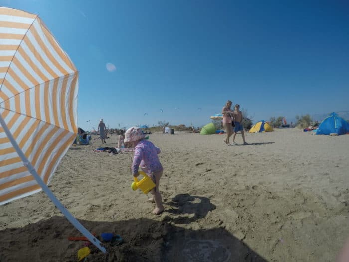 kleines zwei jähriges Mädchen am Strand mit Sonnenhut und UV-Shirt hat eine gelbe Gießkanne in der Hand, links ein orange weuß gestreifter Sonnenschirm