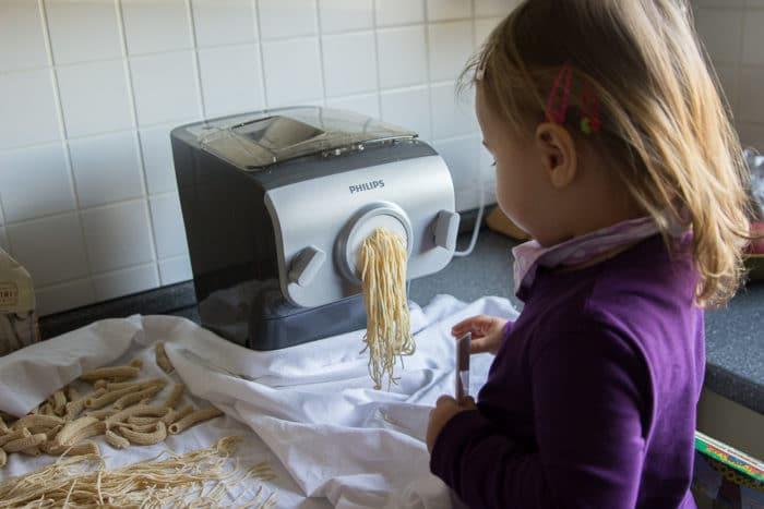 Mädchen steht auf learning tower und hilft beim Nudeln selber machen mit dem Philips Pastamaker - selbstgemachte Spaghetti in wenigen Minuten