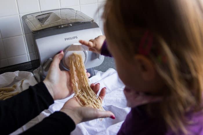 Mädchen bereitet Nudeln selbst zu und hält die aus der Nudelmaschine kommende Pasta fest