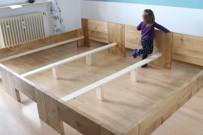 Mädchen steht beim Aufbau des Familienbettes beim aufgebauten Bettgestellt - unser neues großes Familienbett - kein DIY oder IKEA Hack sondern ein gekauftes Familienbett von RIMA
