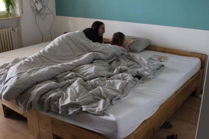 Mama und Tochter liegen auf dem Bauch im großen Familienbett unter der Decke - graue Bettwäsche - lesen zusammen ein Buch zum Thema Schwangershcaft und Geschwister