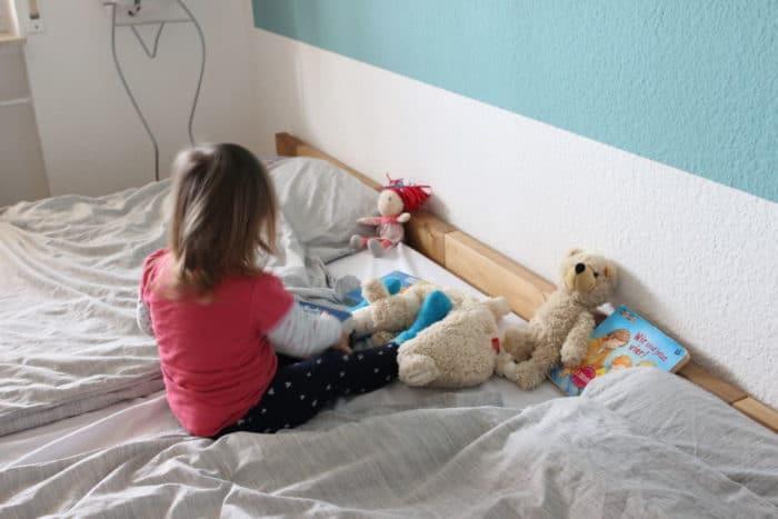 Mädchen sitzt im Familienbett mit Kuscheltieren, Teddy und Puppe