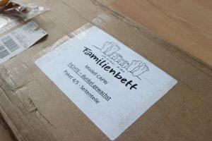 braune Papp Verpackung mit weißem Zettel mit der Aufschrift Original RIMA Familienbett - Modell Capri