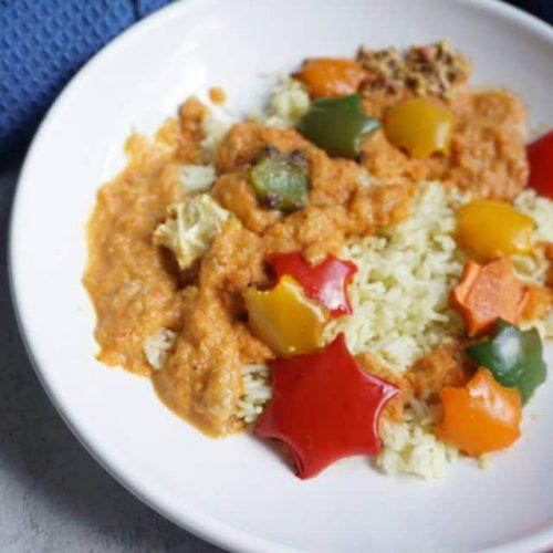 weißer Teller mit Reis und oraangefarbener paprika Zucchini Soße und Sternen aus Gemüse ausgestochen - Gemüsesoße für Kinder