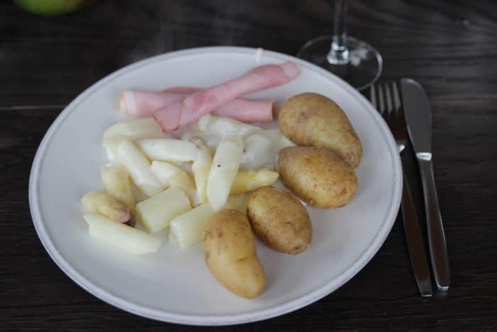 Abendsessen auf einem weißen Teller angerichtet: weißer Spargel geschnitten mit ungeschälten Kartoffeln, heller Soße und Röllchen von gekochtem Schinken