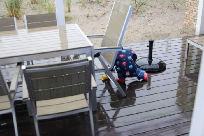 Kind spielt im Regen auf der Tereasse vom Ferienhaus