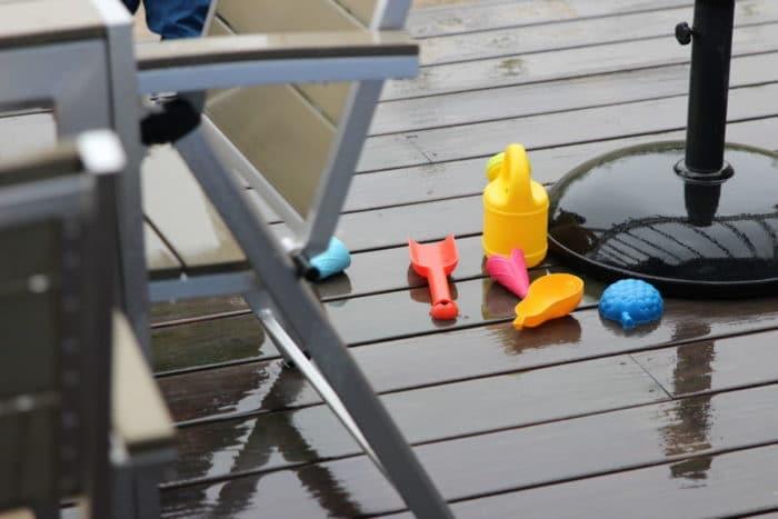 Sandspielsachen liegen im Regen auf der Terasse: Schaufel, Gießkanne und Förmchen
