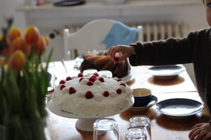 Raffaellotorte mit Himbeeren, Kokosflocken und Raffaello dekoriert auf dem Tisch mit Tulpen, Mamorkuchen. Eine Kinderhand greift nach einer Himbeere