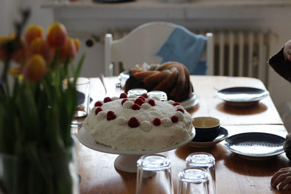 Raffaellotorte mit Himbeeren auf gedeckter Kaffeetafel für den Muttertag mit Tulpen und Mamorkuchen