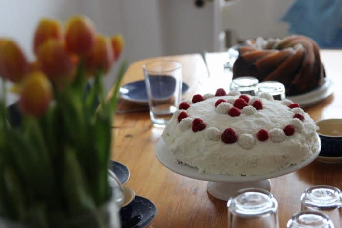 einfache Torte mit Kokos, Sahne und Himbeeren - Rezept für Raffaellotorte mit Himbeeren - Kuchen steht auf dem Tisch für den Muttertag