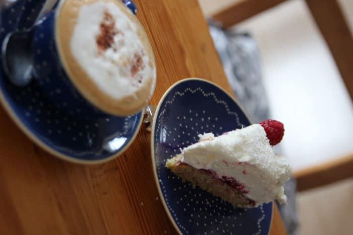 Milchkaffee mit schönem Schaum in einer blauebn Kaffeetasse auf Unterteller nebem einem blauen Kuchenteller mit einem Stück Torte - Raffaellotorte mit Himbeeren - köstliche Kuchen und Torten fürs Wochenende, Geburtstag, Muttertag oder Valentinstag
