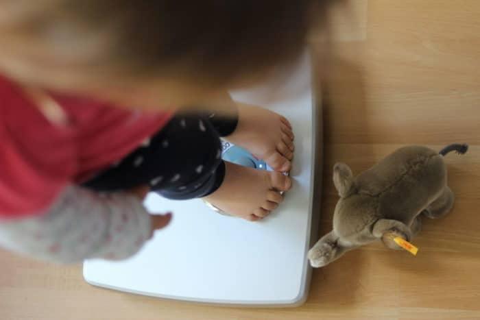 Mädchen steht auf der Waage mit kleinem Kuscheltier Elefant zu ihren Füßen - Wachstum bei Kindern im Blick behalten