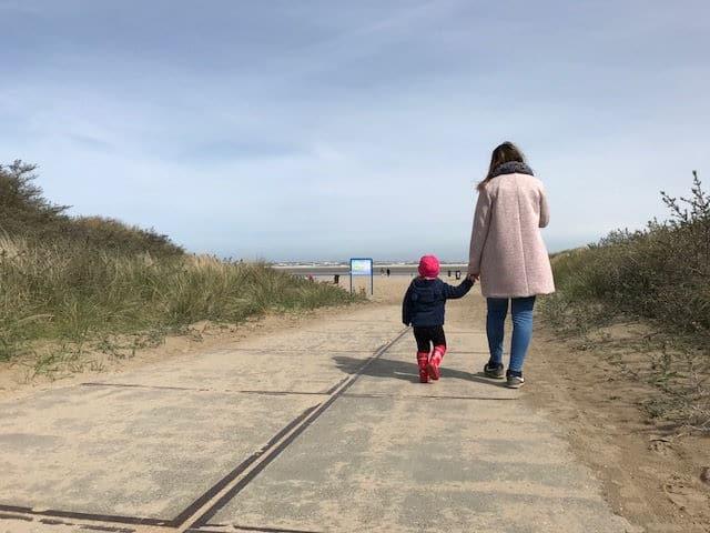 Mama und Kind von hinten, Hand in Hand Spaziergang zum Meer