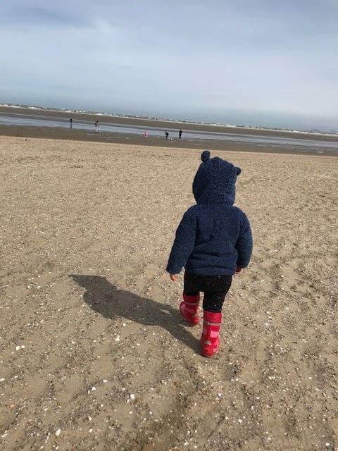 Kind von hinten mit roten Gummistiefeln und blauer Fleecejacke mit Öhrchen läuft durch Sand am Strand in Südholland