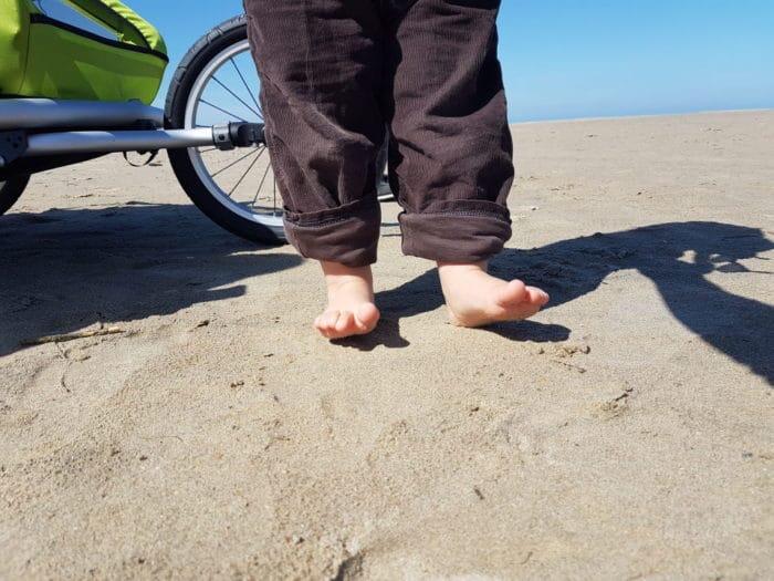 kleine nackige Kinderfüße stehen im Sand am Strand