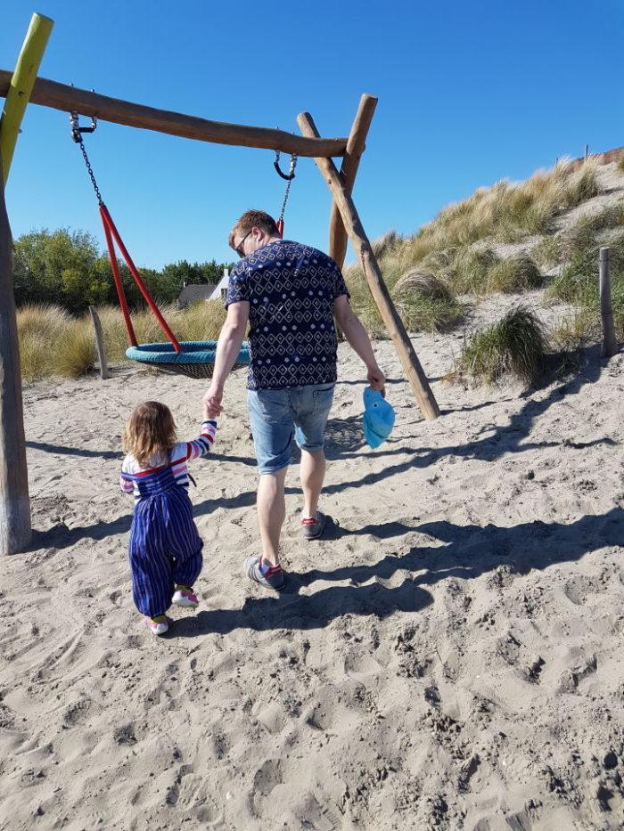 Papa und Mädchen auf dem Spielplatz auf dem Weg zur Schaukel im Landal Strand Resort Ouddorp Duin