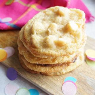 White Chocolate Macadamia Cookies auf einem Holzbrett mit Tuch in pink und buntem Konfetti