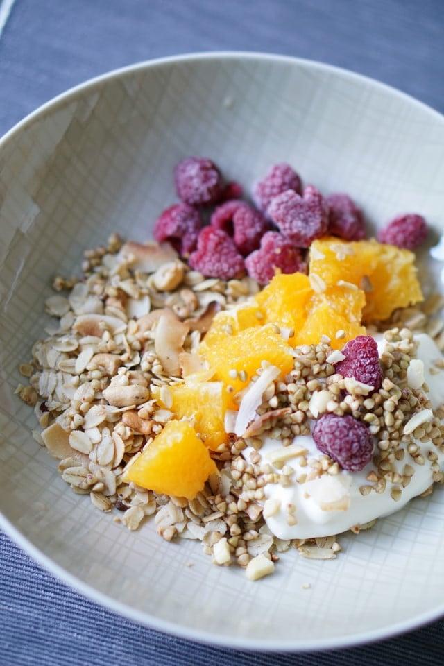 Frühstücksteller mit Müsli ohne Zucker, Orangenstücken und Himbeeren sowie Joghurt und selbstgemachtem Granola, zuckerfrei - ein gesundes Frühstück als Empfehlung für die Louwen Diät am Ende der Schwangerschaft