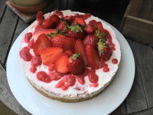 No bake Kuche mit Erdbeeren und Erdbeerpüree auf einem großen weißen Teller