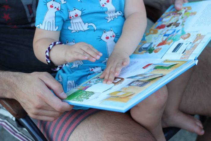 Mädchen liest im Buch Müllabfuhr aus der Kinderbuch Reihe Was ist was Kindergarten für Kinder ab 2 oder 3 Jahren