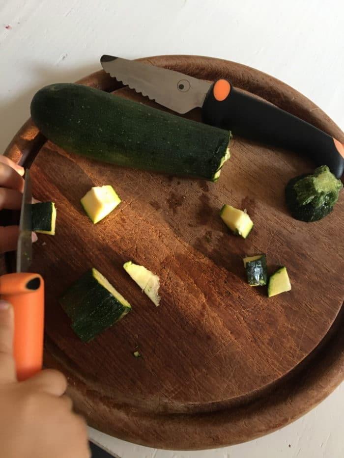 Zucchini werden geschnitten mit dem Kindermesser. Messer für Kinder sind ab etwa 2 Jahren super geeignet. Wir zeigen dir, welches Messer meine Tochter gerne benutzt um ihr Gemüse uns Obst selber zu schneiden. Die Feinmotorik wird traineirt und Verantwortung übernommen