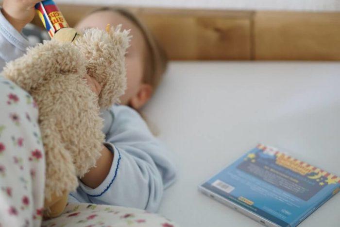 Mächen im SChlafanzug mit Kuscheltier Teddy und CD im Familienbett