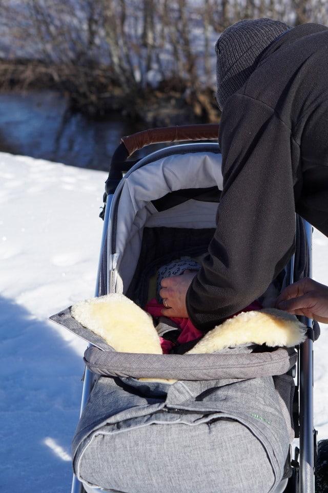 Papa und Baby im Kinderwagen - kuschelig warm hält der Kinderwagenfußsack aus Lammfell vom Fellhof