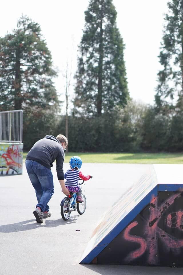 Papa und Tochter beim Fahrradfahren lernen - unserer 15 Tipps, wie du dein Kind entspannt und bedürfnisorientiert begleiten kannst beim Fahrradfahren lernen.